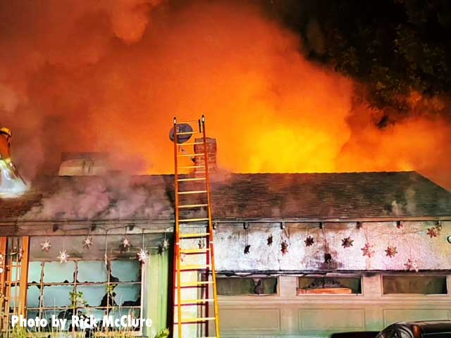 The light from flames on the roof with smoke and a ladder