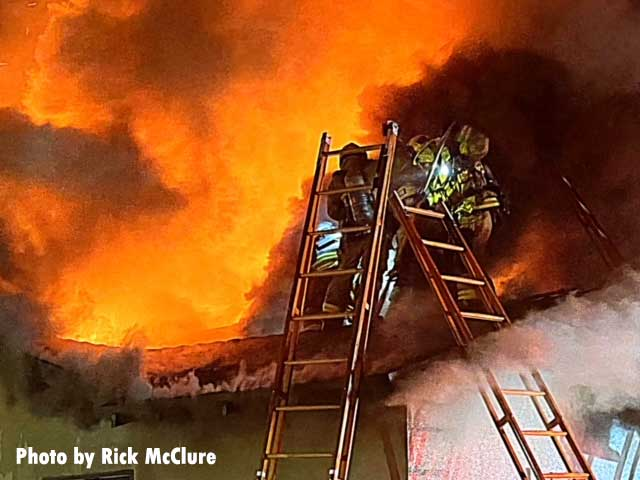 Two ladders nearly meeting atop a roof at a house fire with firefighters on the roof