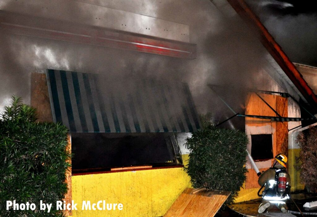 LAFD firefighter trains a hoseline into the interior of the building