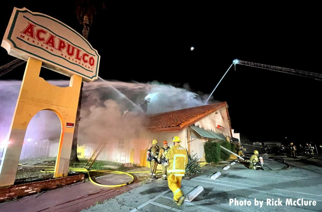 Firefighters and aerial streams at scene of Los Angeles fire in a boarded-up restaurant