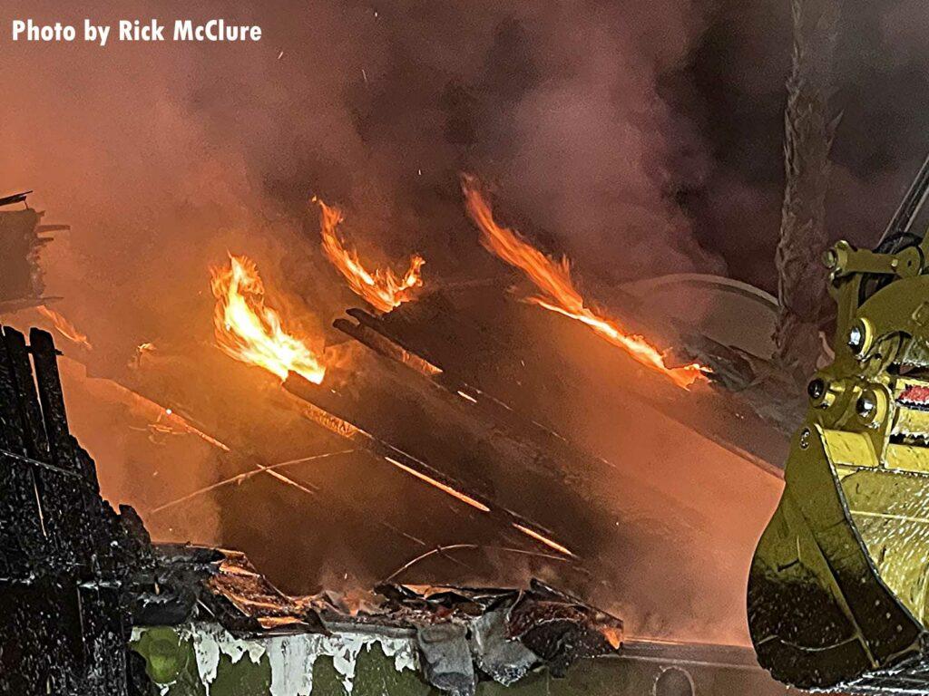 Bulldozer turning over flaming debris