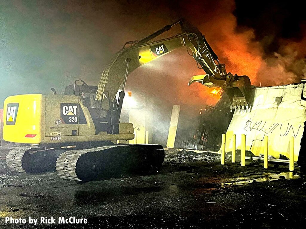 A Caterpillar excavator being used to knock down flaming debris