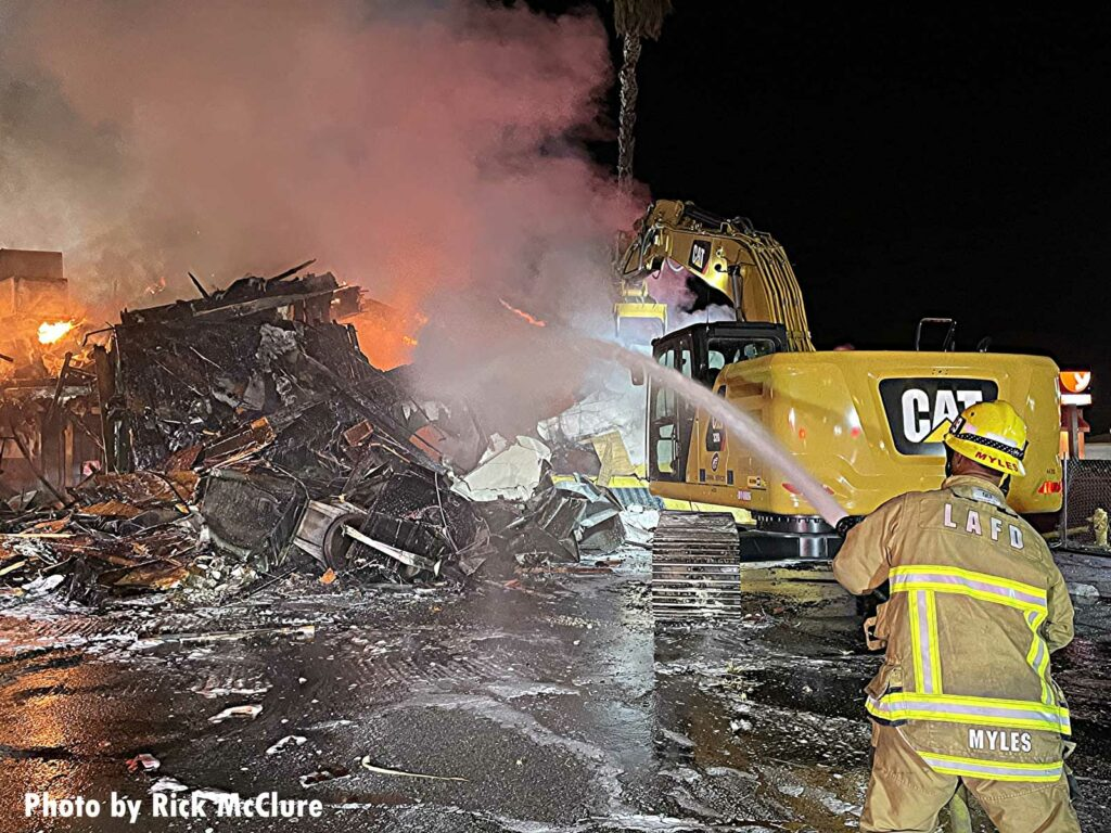 Firefighter puts water on the debris as excavator turns the pile