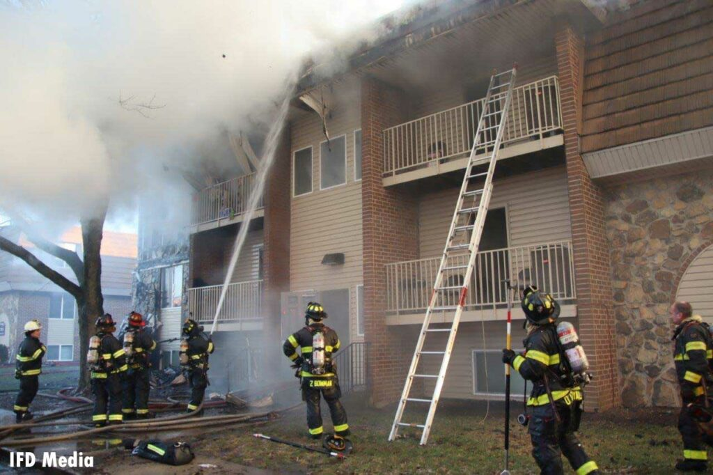 Firefighter puts a hose stream on the roof of an apartment fire with ladder extended up the balcony