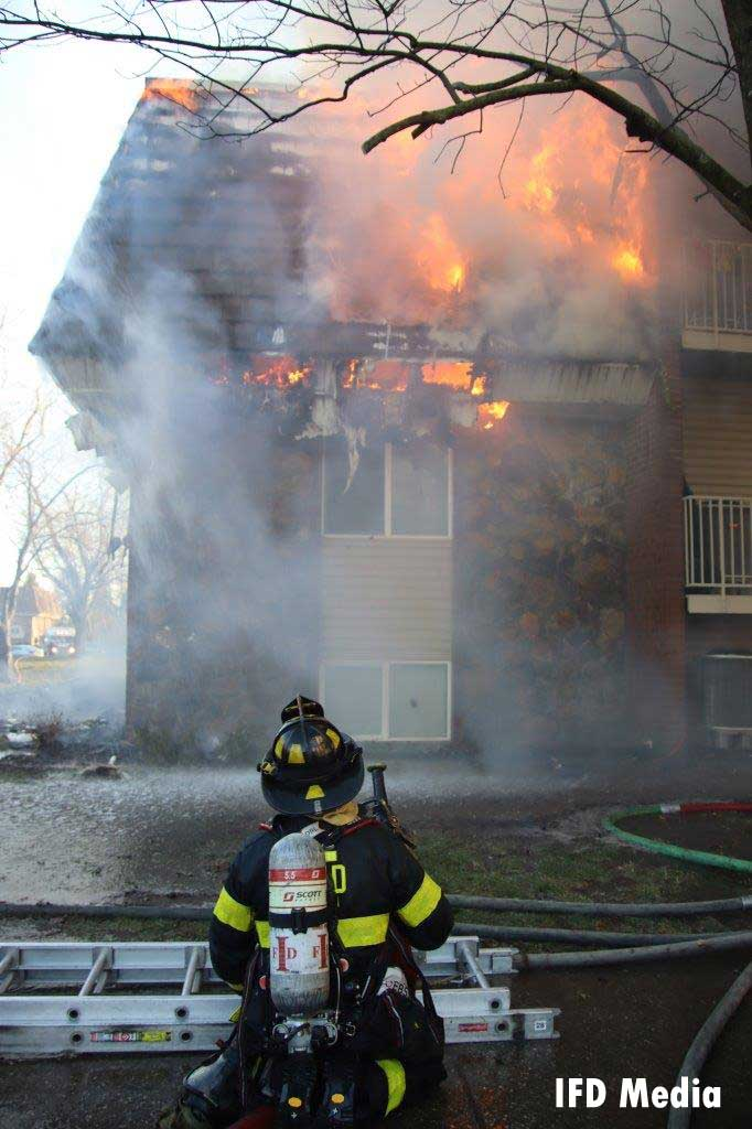 Firefighter with a ladder observing flames shooting from an apartment building