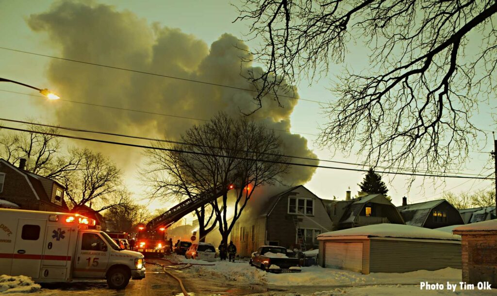 Chicago aerial and ambulance on scene at a house fire with smoke drifting into the sky