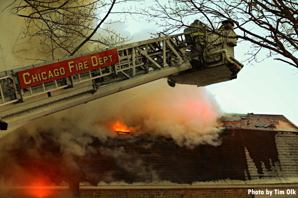 Chicago Fire Department tower ladder extended at fire with flames coming through the roof