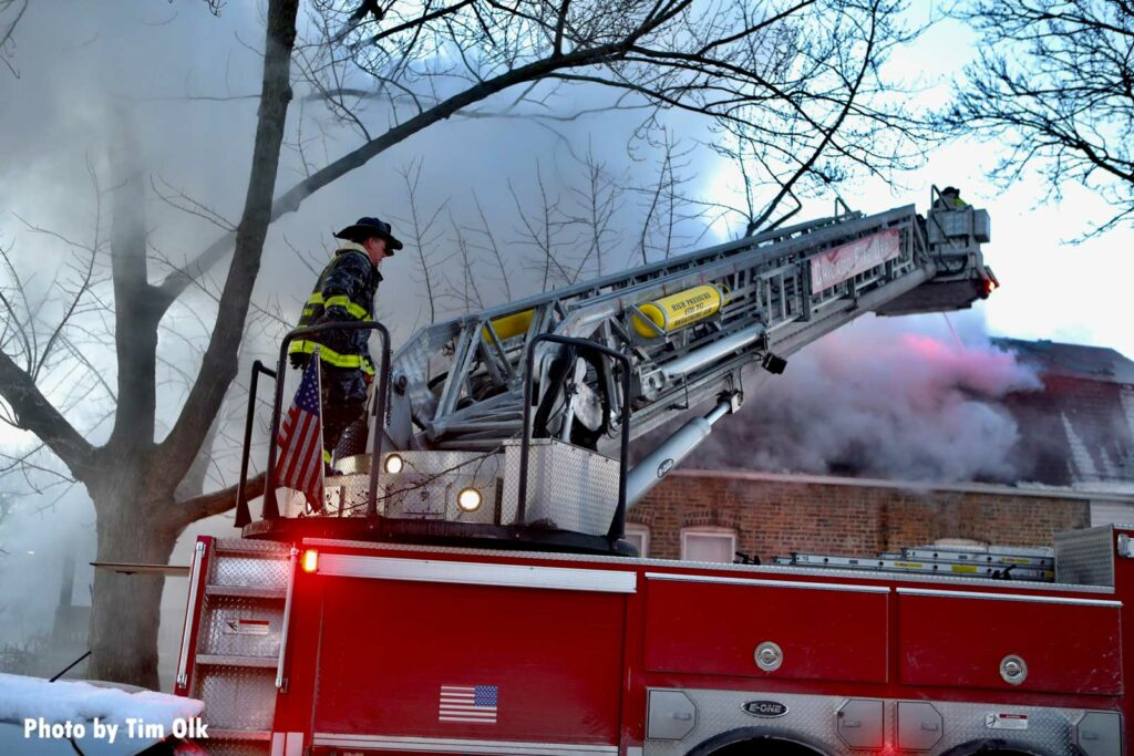 Chicago firefighters on a tower ladder with smoke coming from the home
