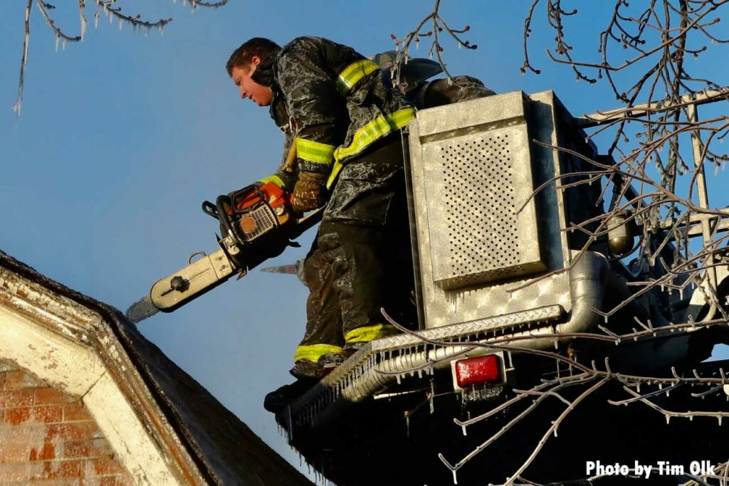 Chicago firefighter with a chainsaw operating from a tower ladder bucket