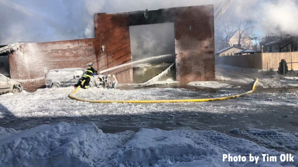 Firefighter puts water stream into collapse building in Hammond