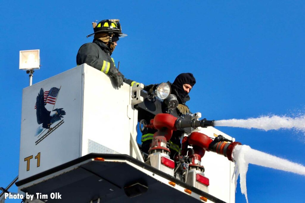 Firefighters in a tower ladder bucket flowing water