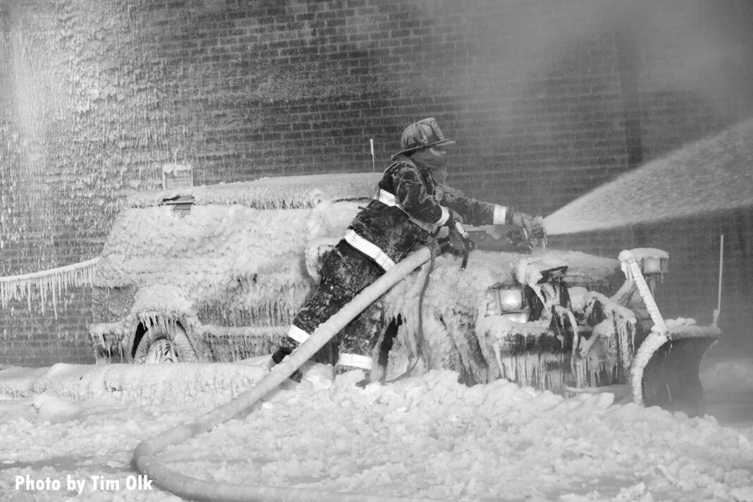 Firefighter leaning over a car covered with icicles with a portable master stream