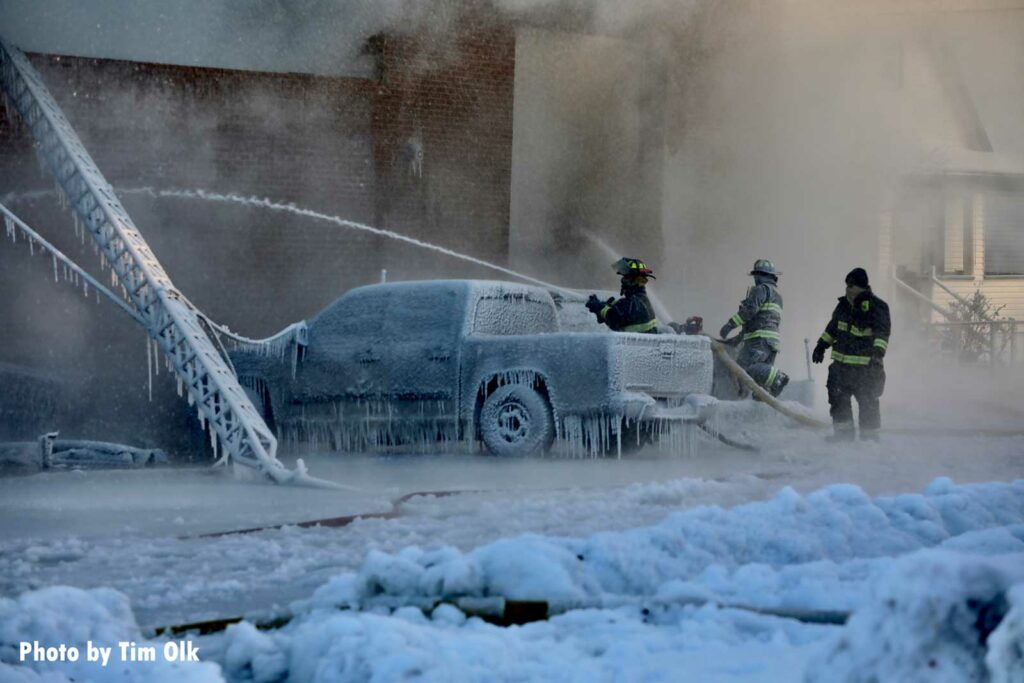 Icicles cover a vehicle as firefighters train a hoseline on the fire