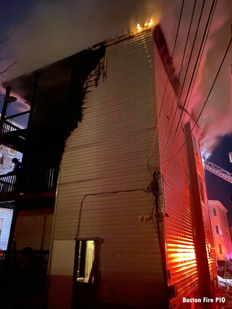 Burned side of the structure with fire on the roofline