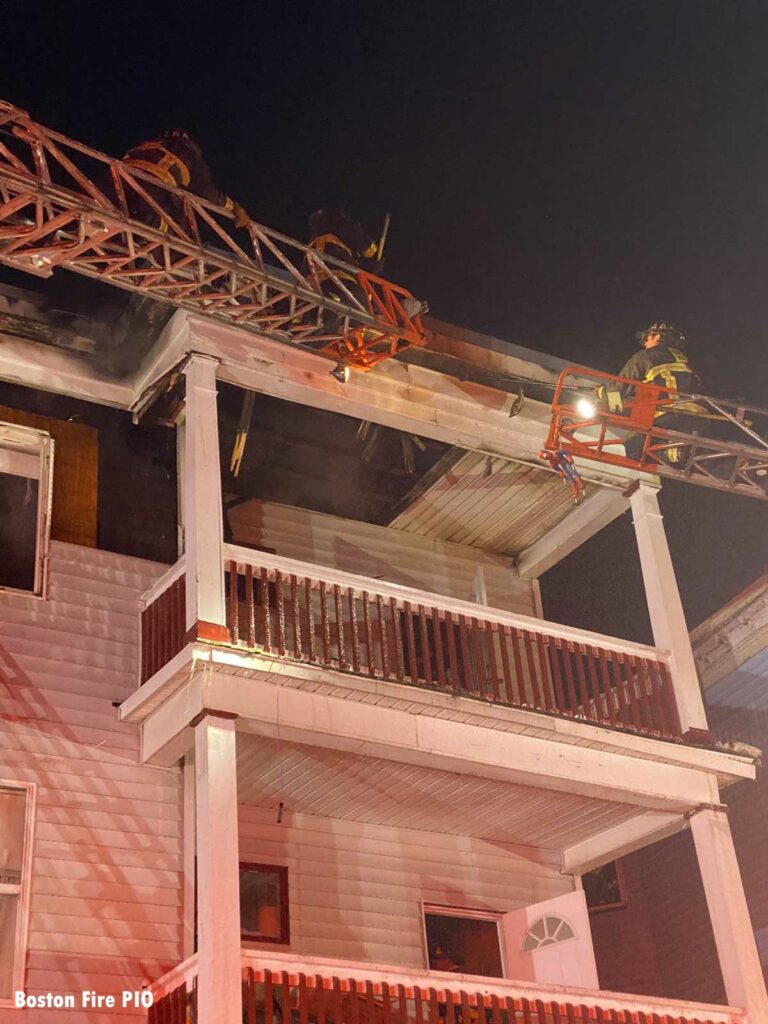 Two firefighters on aerial ladders at the scene of the fire in Boston