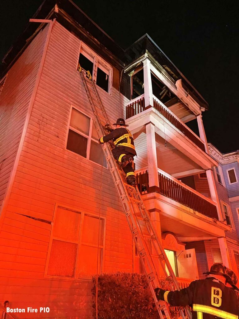 Boston firefighter on a portable ladder at the fire