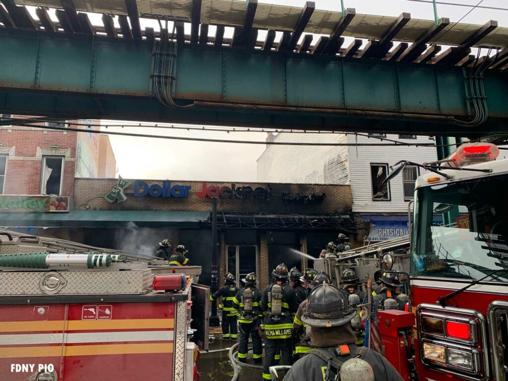 Burned out building with FDNY firefighters on scene under the elevated rail in Queens