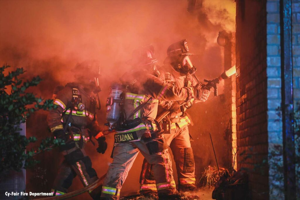 Firefighters train a hoseline onto the interior of a house fire