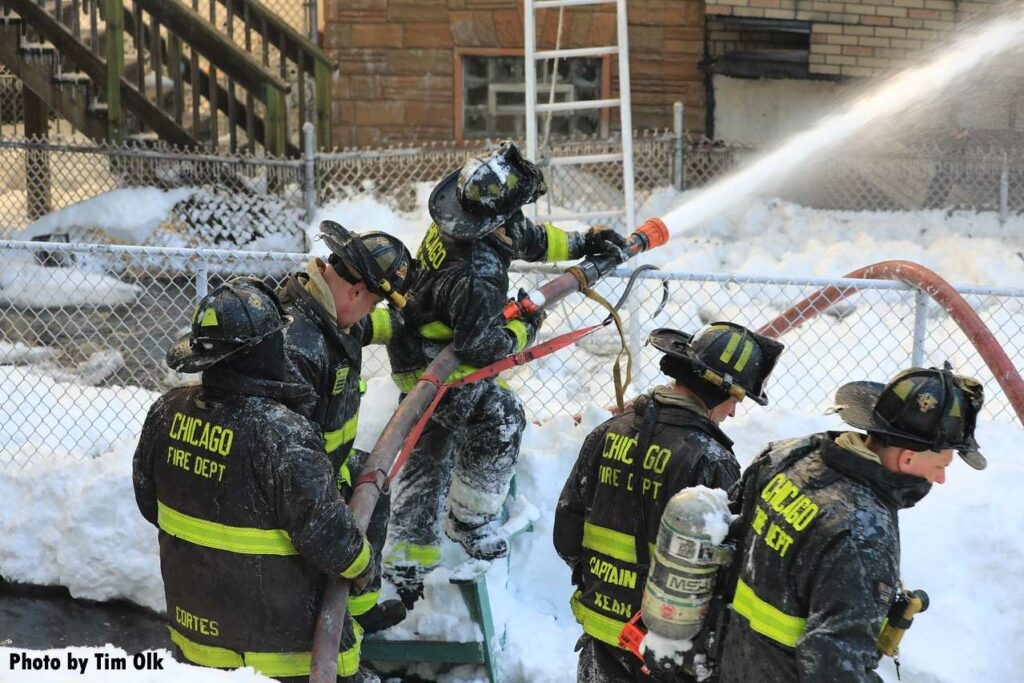 Chicago firefighters manipulate an exterior stream on the fire