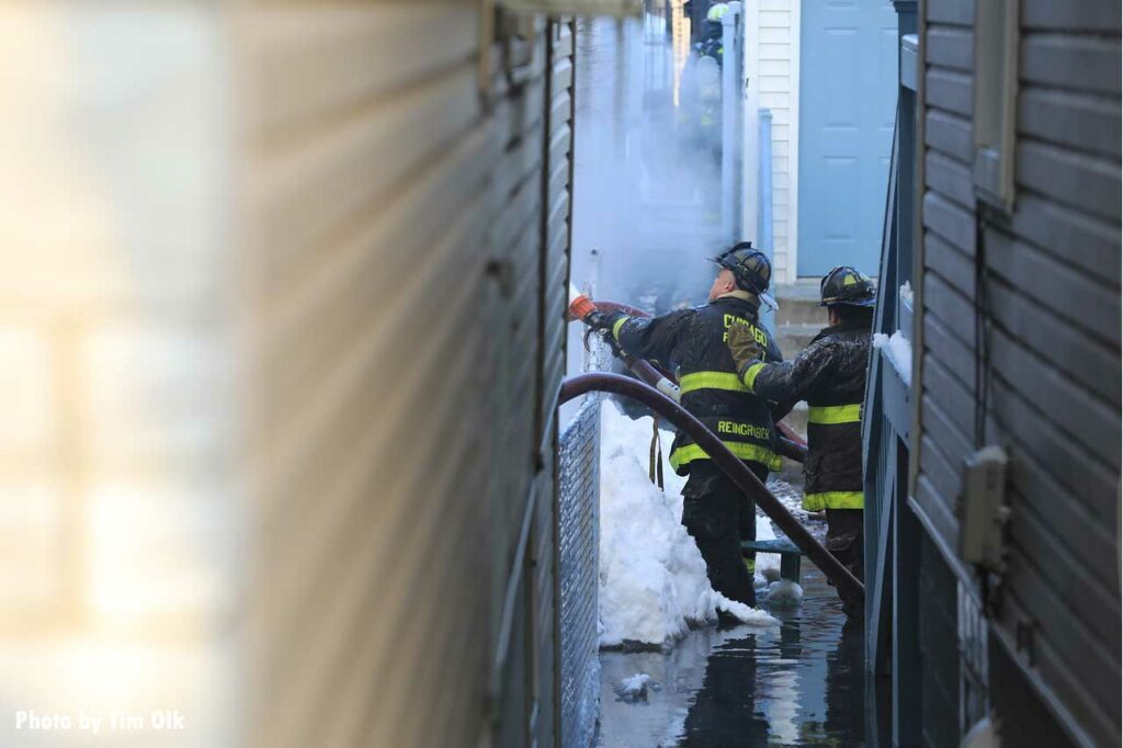 As seen from down an alleyway, Chicago firefighters advance a hoseline