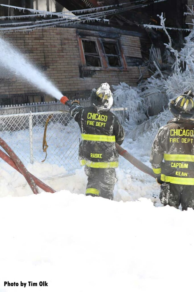 Chicago firefighters with a hoseline in the snow