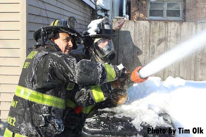 Chicago firefighters, one covered in snow, train a hoseline on the fire building