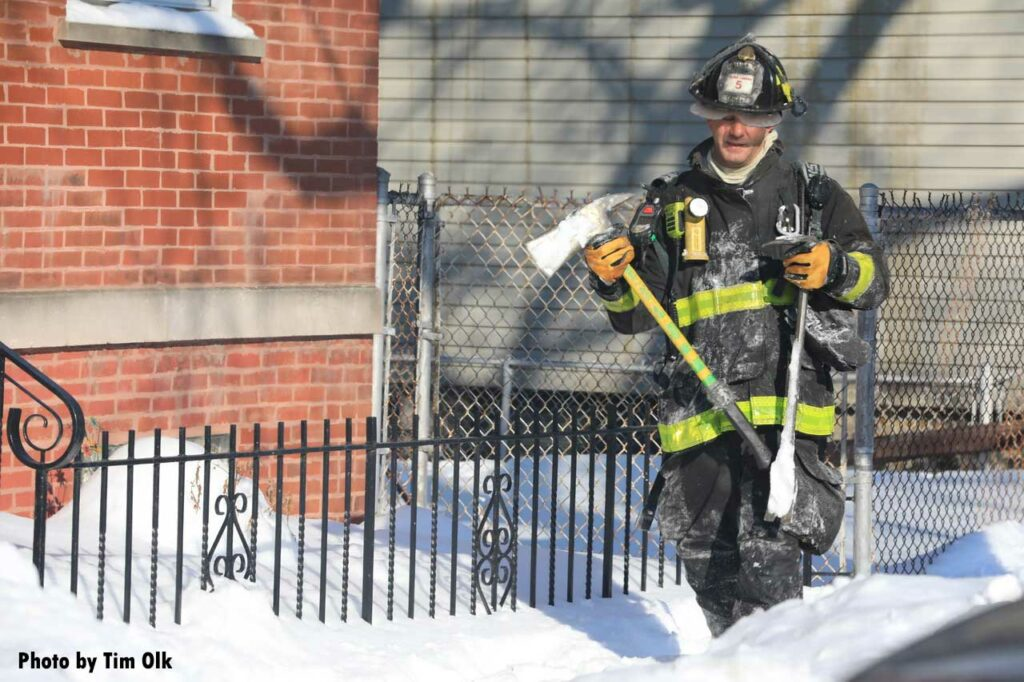 Firefighter carrying an ax and a halligan at fire