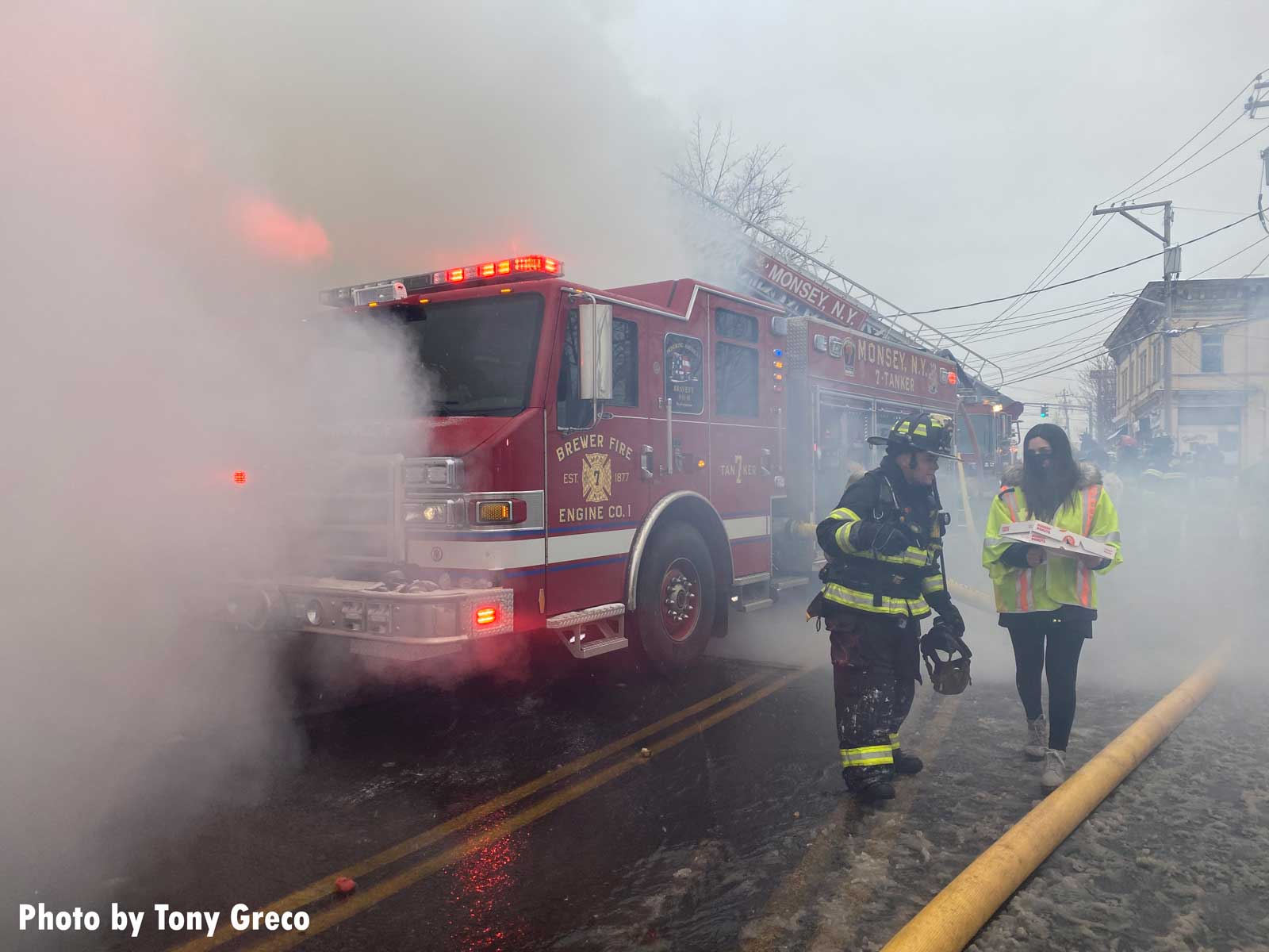 Firefighters at the scene of a Monsey fire, with rig partly enveloped by smoke