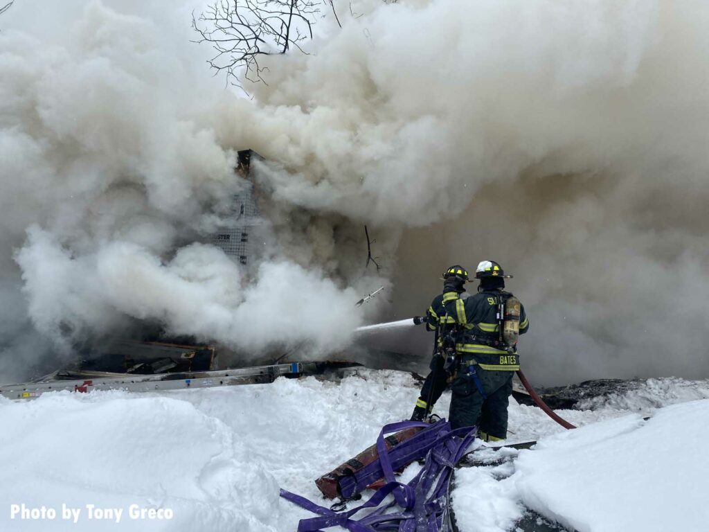 Smoke billows as firefighters train a hoseline on the building