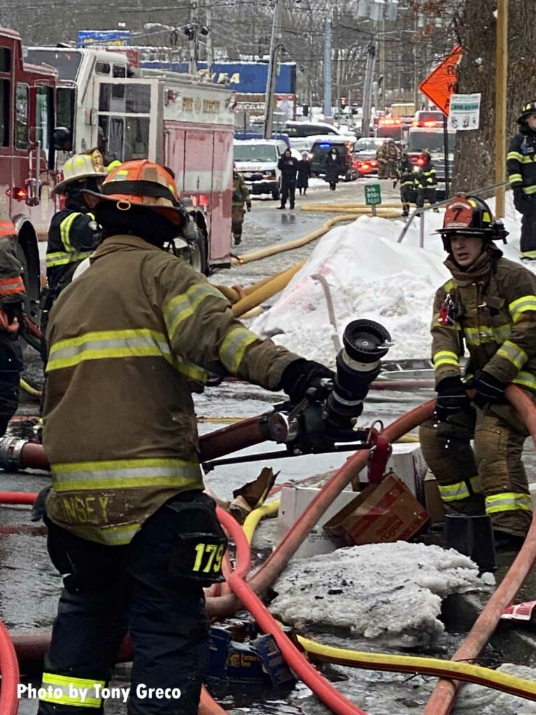 Firefighters move hoseline at the Monsey fire scene
