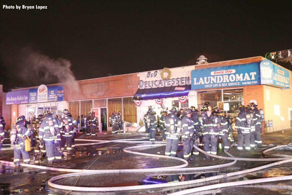 Firefighters with hoseline outside fire that impacted multiple businesses