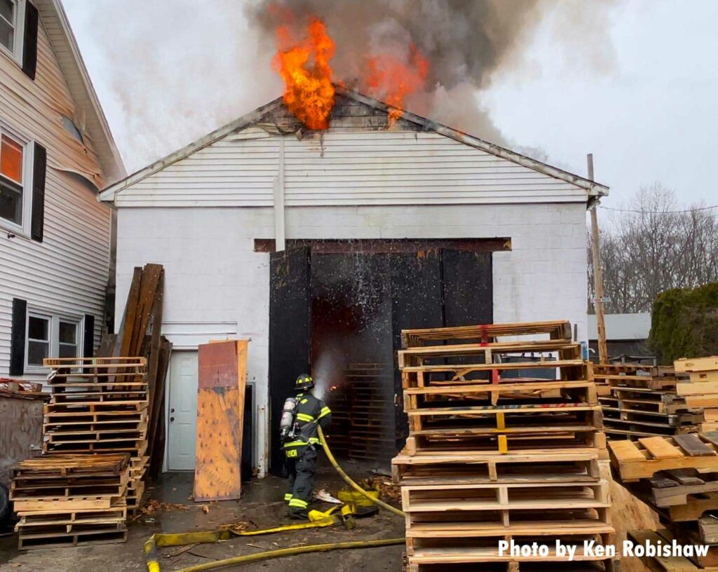 Firefighter directs a hose stream into a building with fire along roofline