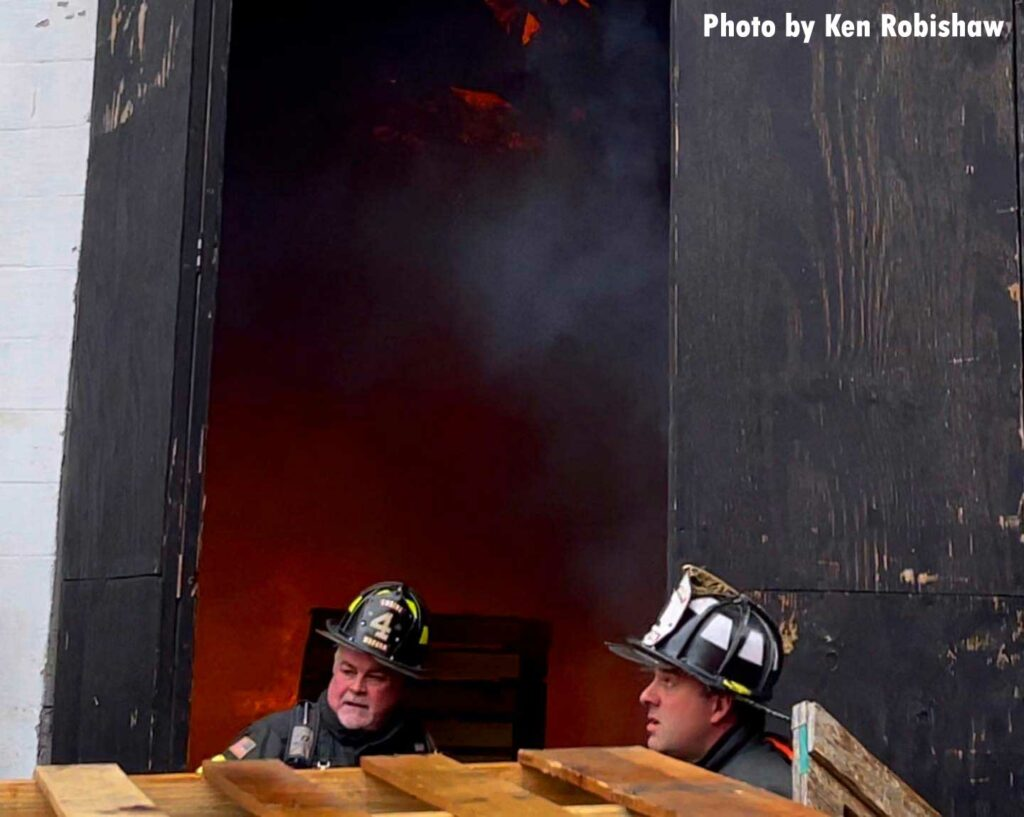 Two firefighters outside the doors of the garage with smoke showing