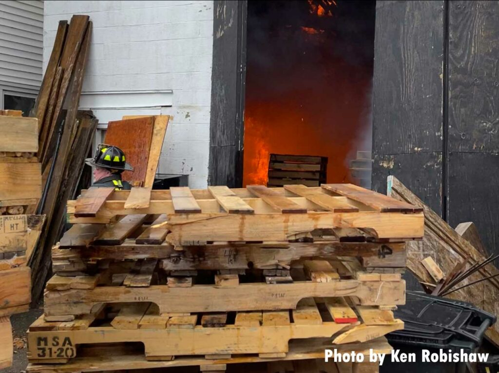 Firefighter with pallets as flames reflect in the interior of the building