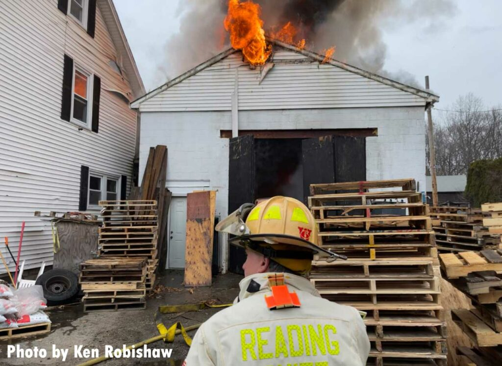 Reading firefighter with the building in the background and fire showing from the roof