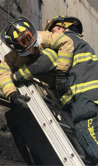 Firefighters should slide their hands down the back of the rails so they don't lose contact with the ladder while transporting a victim.