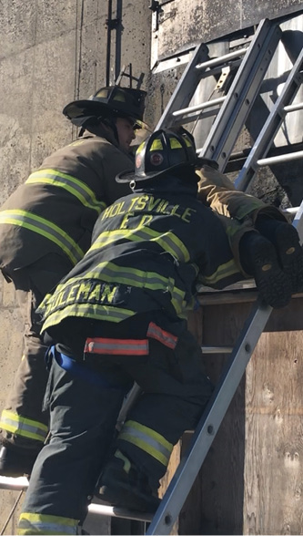 A firefighter operating on an adjoining ladder is trying to support the victim and take some of the weight off the firefighter carrying the bulk of the victim's weight.