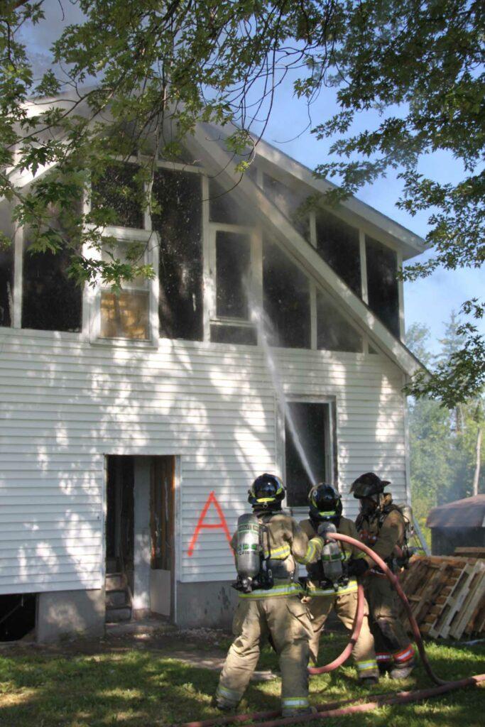 Firefighters train a hose stream on window