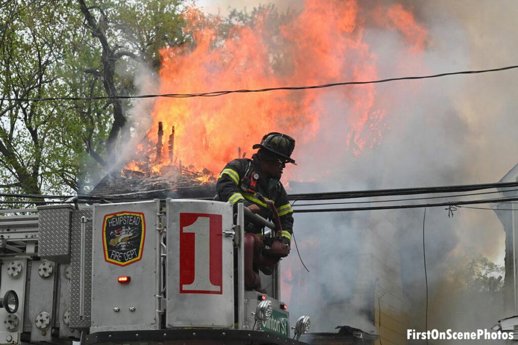 Firefighter in the bucket of Hempstead Fire Department Truck 1 as flames roar behind him