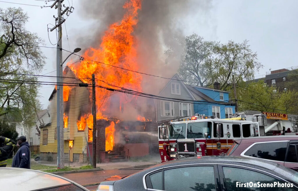 Flames tear through a home on the corner in Hempstead, New York, with a fire apparatus in front