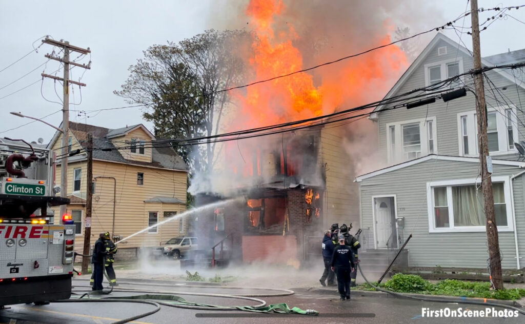 Firefighter puts an exterior stream on a fire raging in an abandoned home