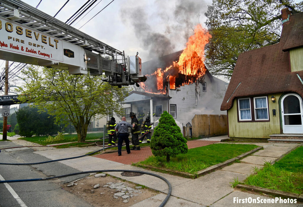 Roosevelt NY Fire Department tower ladder and firefighters at scene of raging house fire
