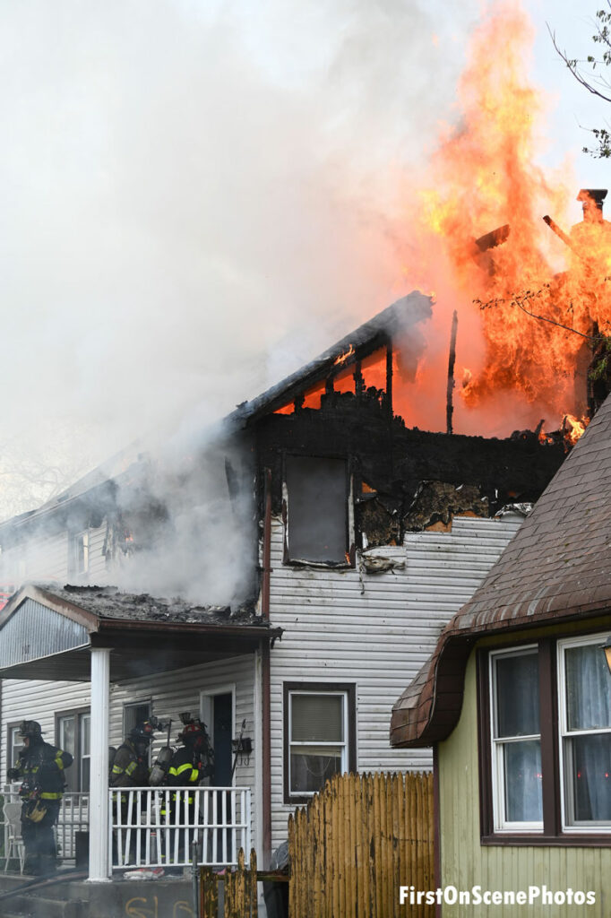 Firefighters push into the fire building as flames consume the second floor and shoot up into the sky