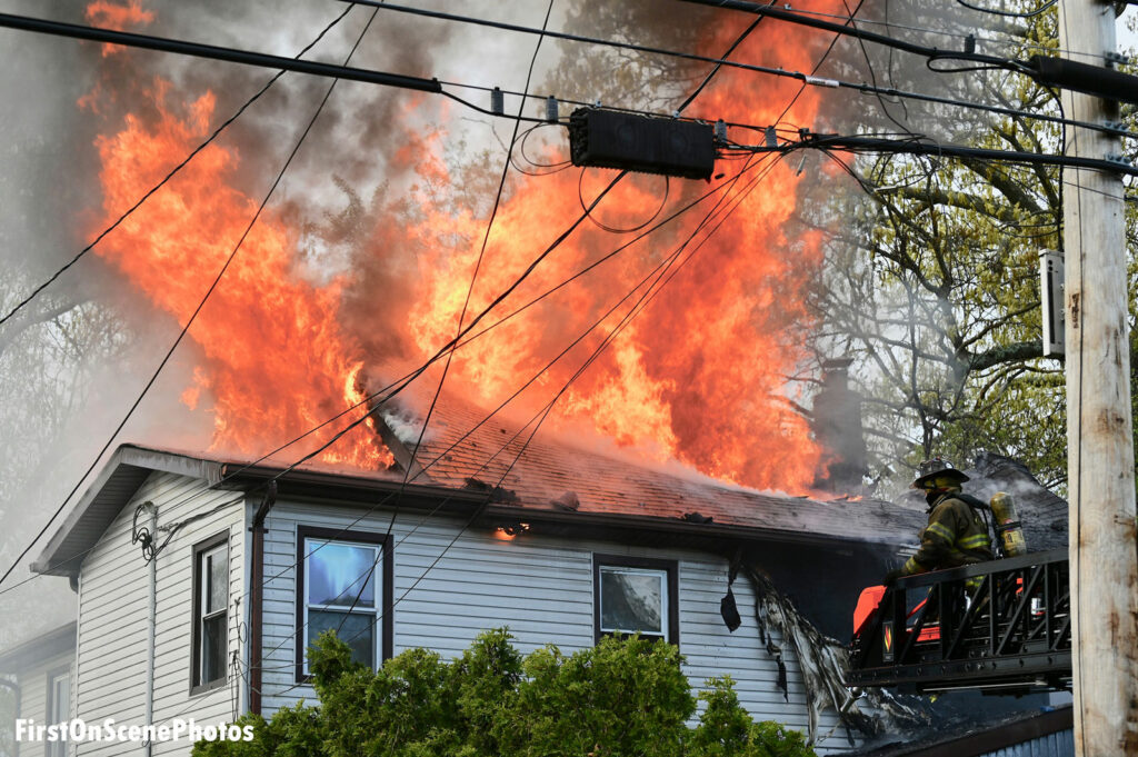 Flames shoot up through the roof of a home on Long Island while a firefighter works from the aerial ladder