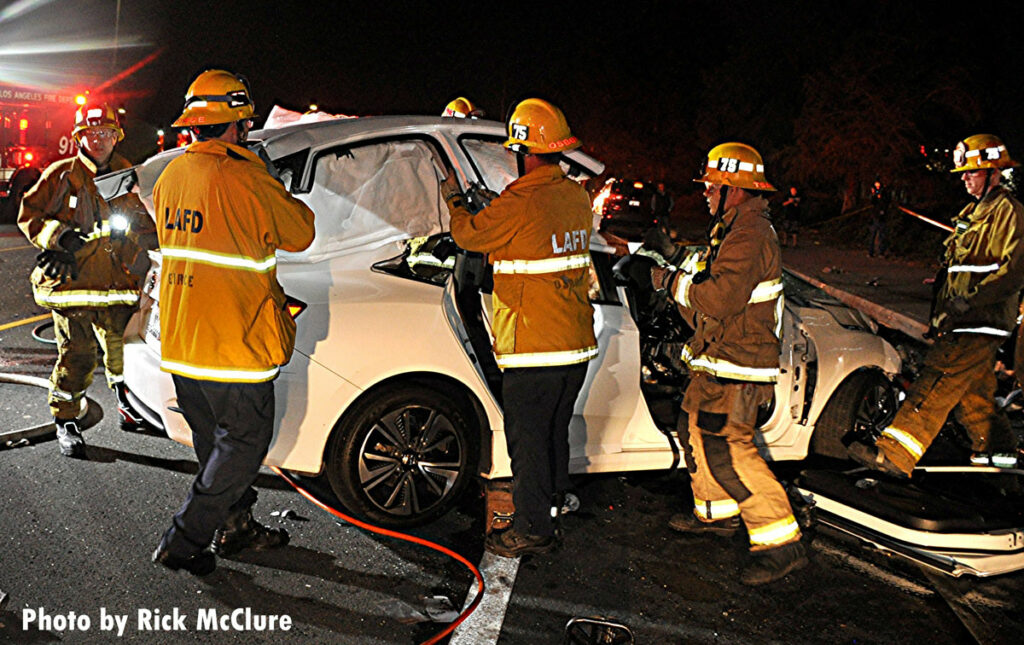 Firefighters lift the roof off a vehicle at crash scene