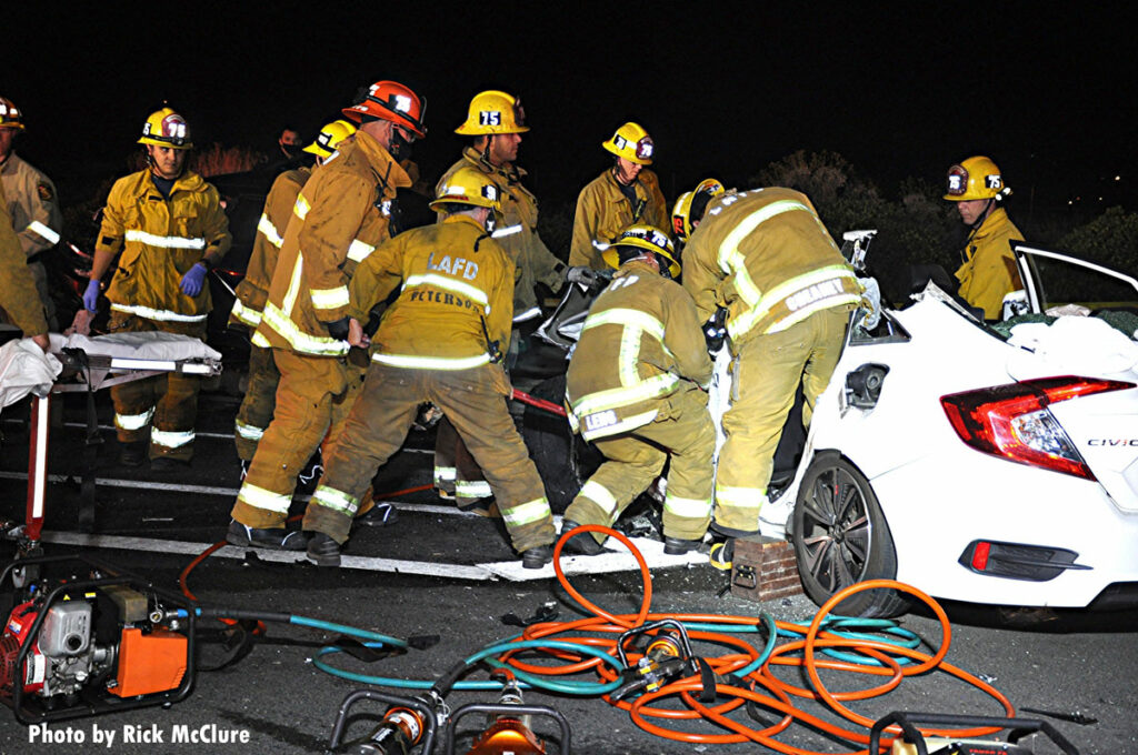 Firefighters work to remove a victim from a crash scene in Los Angeles