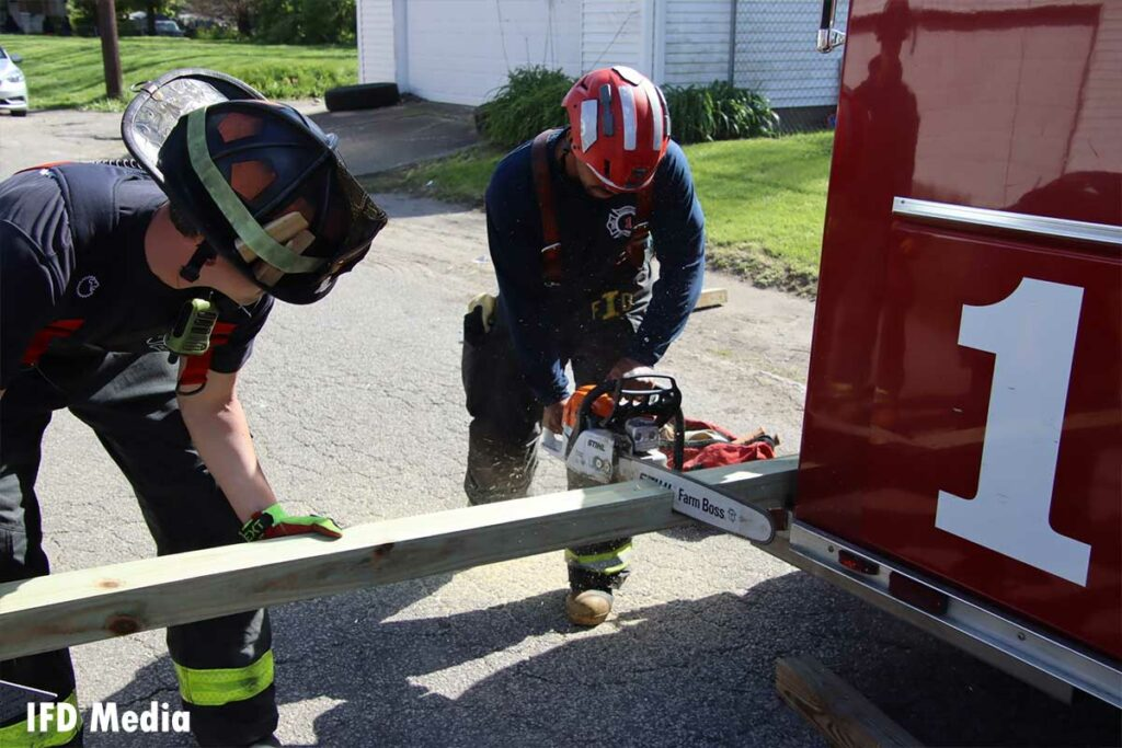 Firefighters use a chainsaw to cut wood on the back of the vehicle