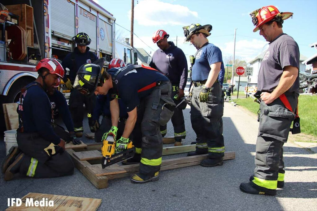 Firefighters use a drill to put together the shore support system