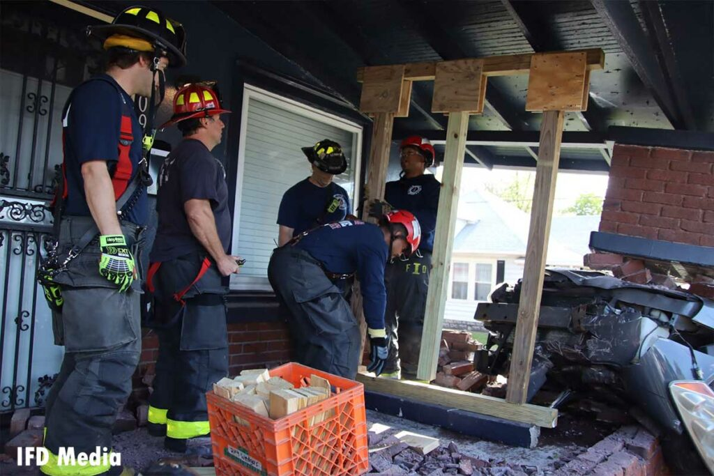 Firefighters place the shoring device in place on the damaged porch