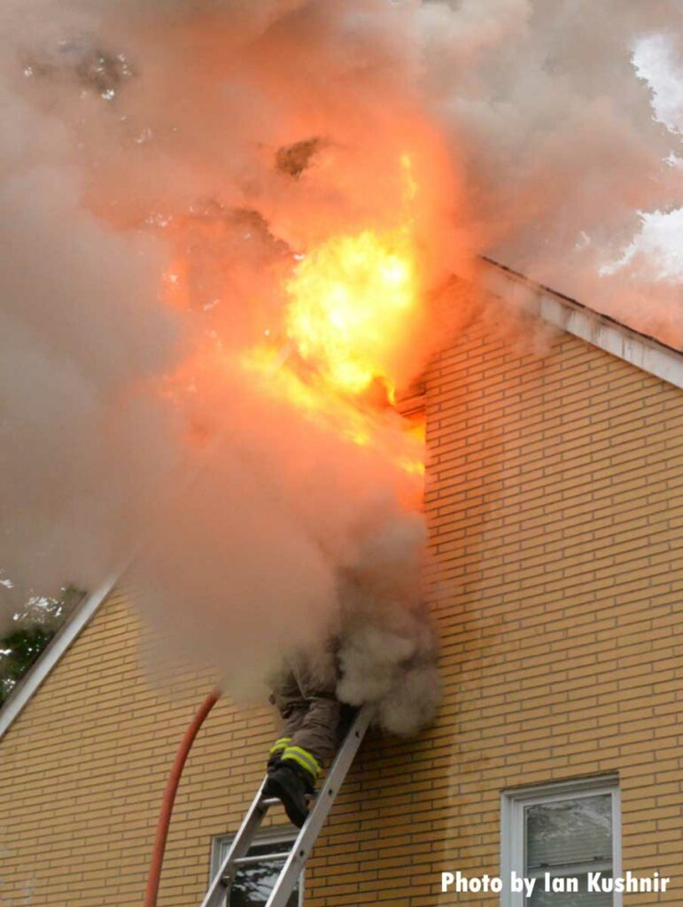 A firefighter with a hoseline on a ladder is engulfed by smoke and flames